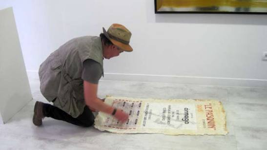 Juan Rafael, preparando el cartel para colocarlo en la galería. © Eloísa Otero.
